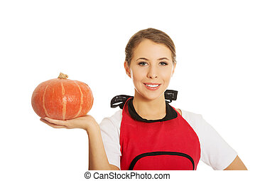Young woman holding a pumpkin
