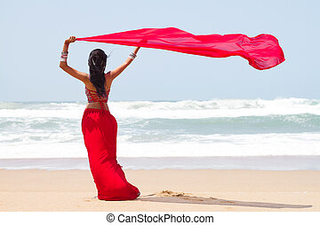 young woman holding a sarong on windy beach
