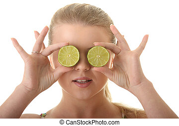 Young woman holding a slice of lemon in front of her eye
