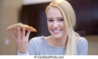 Young woman holding a slice of pizza
