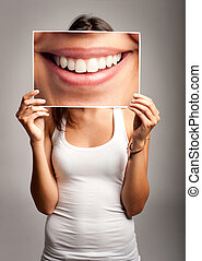young woman holding a smile - young woman holding a picture...