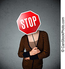 Young woman holding a stop sign - Young lady standing and...