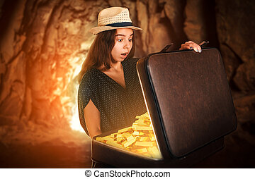 Young woman holding a suitcase full of gold bars.