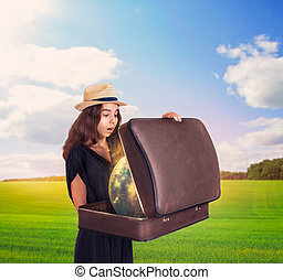 Young woman holding a suitcase with magic globe.
