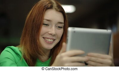 Young woman holding a tablet computer, looking at screen and smiling, saying something.