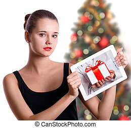 young woman holding a tablet with photo of christmas presents