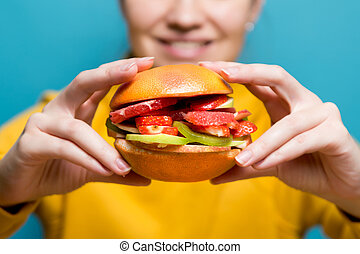 young woman holding a vegetarian burger made of fruits and berries
