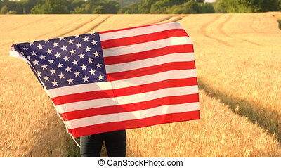 Young woman holding an American USA Stars and Stripes flag in a wheat field at sunset or sunrise