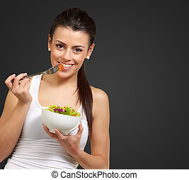 Young woman holding and eating salad