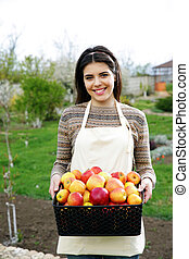Young woman holding basket with apples in garden