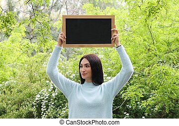 Young woman holding blank black chalkboard sign with copy space in hands over her head in green park