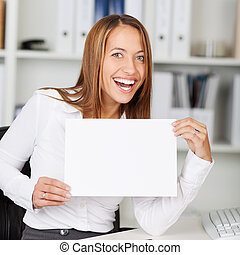 Young Woman Holding Blank Paper At Desk