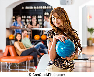 Young Woman Holding Blue Bowling Ball in Club