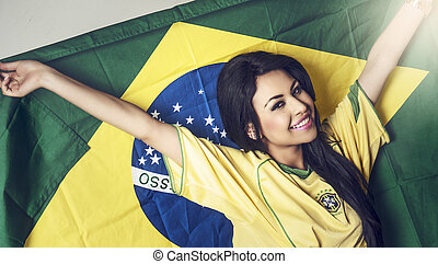 Young woman holding Brazil flag