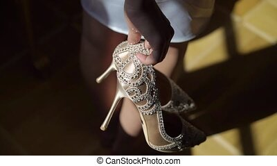 Young woman holding bridal wedding shoes