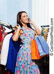 Young woman holding chosen clothes with mobile