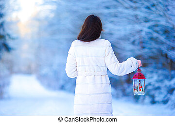 Young woman holding Christmas lantern outdoors on beautiful winter snow day