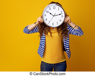 young woman holding clock in front of face