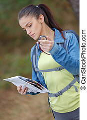 young woman holding compass and map