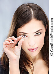 contact lens - Young woman holding contact lens with two...