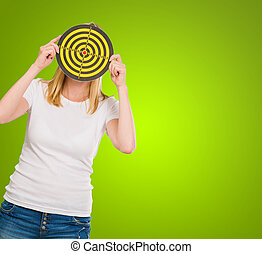 Young Woman Holding Dartboard In Front Of Face