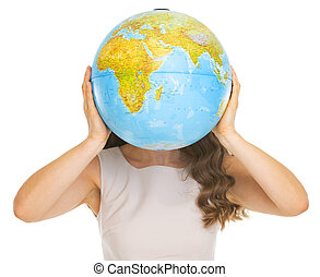 Young woman holding earth globe in front of face