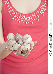 Young woman holding garlic in her hand