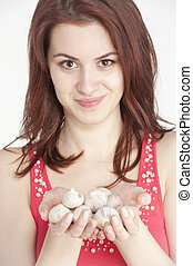 Young woman holding garlic in her hands