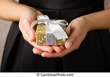 Young woman holding gift box with bow, close up