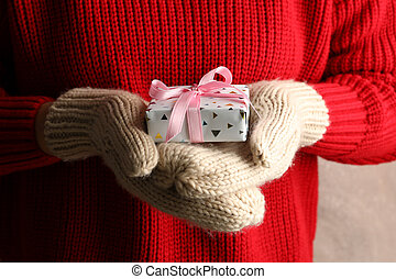 Young woman holding gift box with pink bow, close up