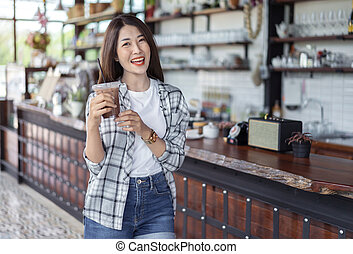 woman holding glass of iced chocolate milk in a cafe