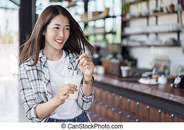 woman holding glass of iced milk in a cafe