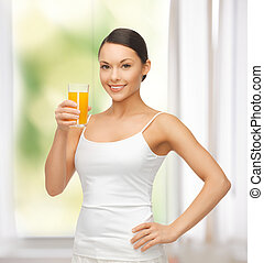 woman holding glass of orange juice - young woman holding ...