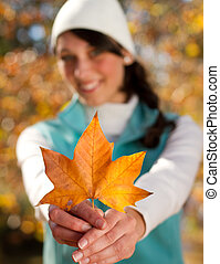 young woman holding golden tree leaf outdoor in forest