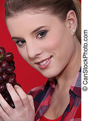 Young woman holding grapes