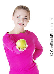 Young woman holding green fresh apple in hand