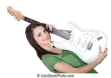 Young woman holding guitar on white background