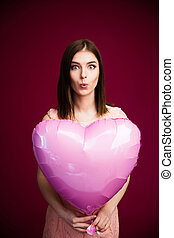 Young woman holding heart shaped balloon over pink...