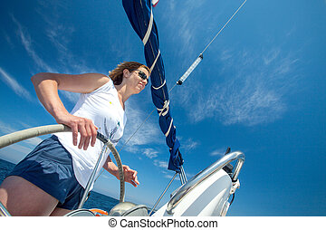 Young woman holding helm of a boat.