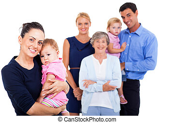young woman holding her baby with extended family on background