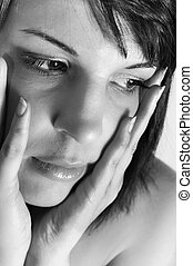 young woman holding her face with hands in black and white
