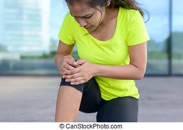 Young woman holding her painful knee