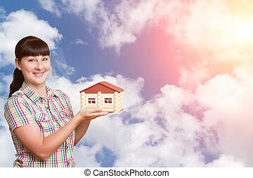 Young woman holding home isolated on a background of sky.