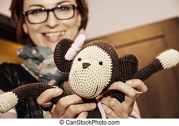 Young woman holding in hands knitted monkey doll. Beauty and...