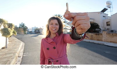 Young woman holding keys while standing outdoor against new house.