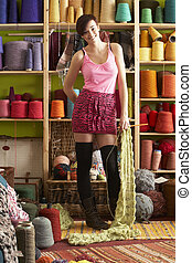 Young Woman Holding Knitted Scarf Standing In Front Of Yarn Display