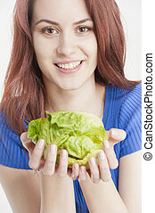 Young woman holding lettuce in her hands