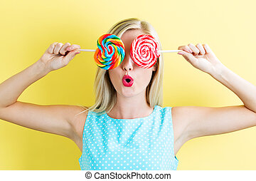 Young woman holding lollipops