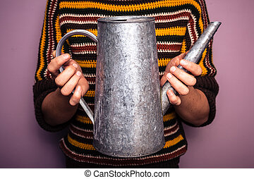 Young woman holding metal watering can