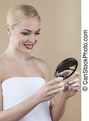 Young woman holding mirror - Using mirror to perfect her...